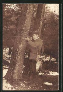 AK Jäger hinter einem Baum stehend, zielt auf seine Beute