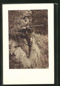 Foto-AK Jäger mit geschossenem Greifvogel auf einem Felsen
