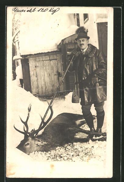 AK stolzer Jäger mit erlegtem Hirsch im Winter