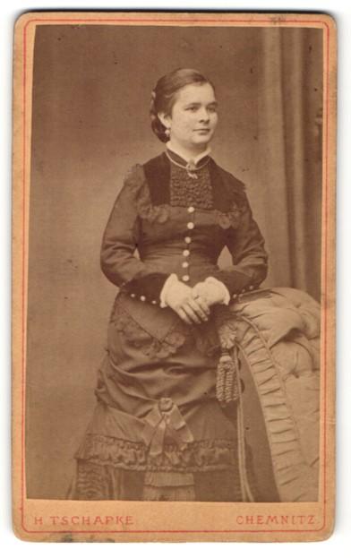 Fotografie H. Tschapke, Chemnitz, charmant lächelnde junge Dame mit Flechtfrisur im prachtvollen Kleid