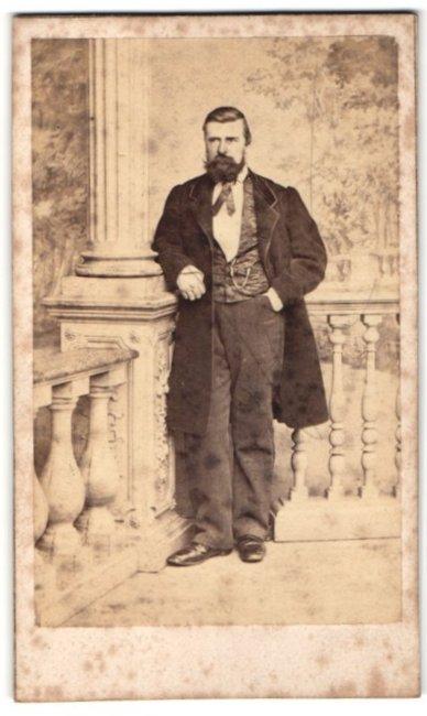 Fotografie Duboso, Abbeville, Mann im schwarzem langen Jacket auf einer veranda posierend