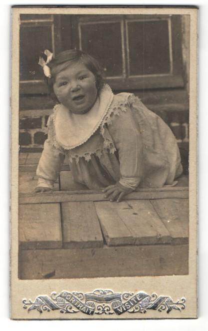Fotografie Portrait Visite, Ort unbekannt, Portrait krabbelndes Kleinkind mit Haarschleife