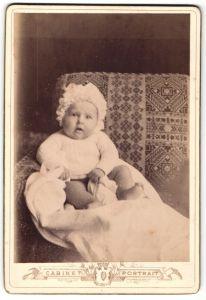Fotografie Cabinet Portrait, unbekannter Ort, kleines Baby in weissem Hemdchem mit Mütze schaut niedlich