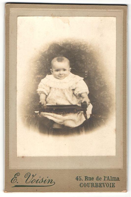Fotografie E. Voisin, Courbevoie, Kleines Baby in weissem Kleidchen sitzt in einem Kinderstuhl