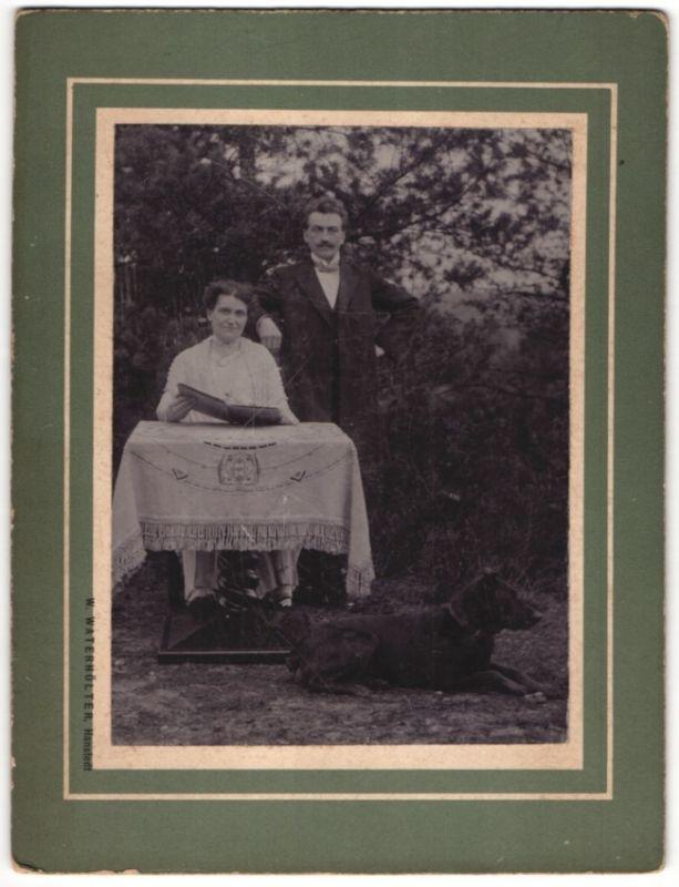 Fotografie W. Waterhölter, Hanstedt, Paar mit Hund & Foto-Album im Garten