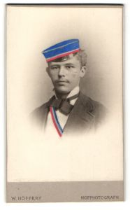 Fotografie W. Höffert, Berlin, Portrait Burschenschaftler mit Mütze und Schärpe, handkoloriert
