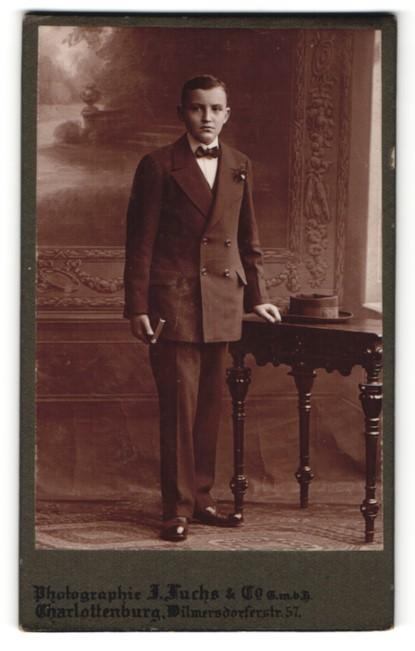 Fotografie J. Fuchs & Co, Berlin, hübscher Knabe im eleganten Anzug mit Buch zur Konfirmation