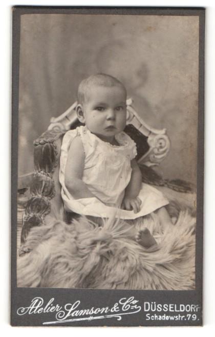 Fotografie Atelier Samson & Co, Düsseldorf, niedliches Baby im weissen Kleidchen auf Felldecke sitzend