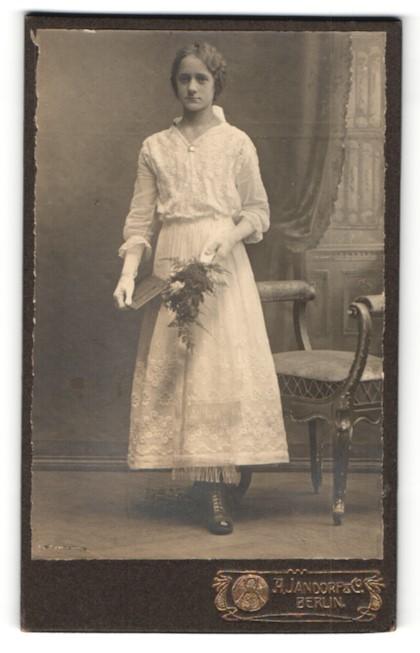 Fotografie A. Jandorf & Co, Berlin, schönes junges Mädchen im bestickten Kleid mit Buch und Blumenstrauss