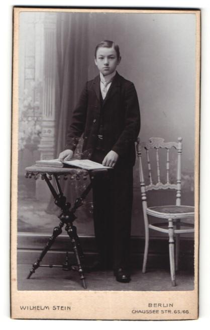 Fotografie Wilhelm Stein, Berlin, Portrait Knabe mit Buch am Tisch