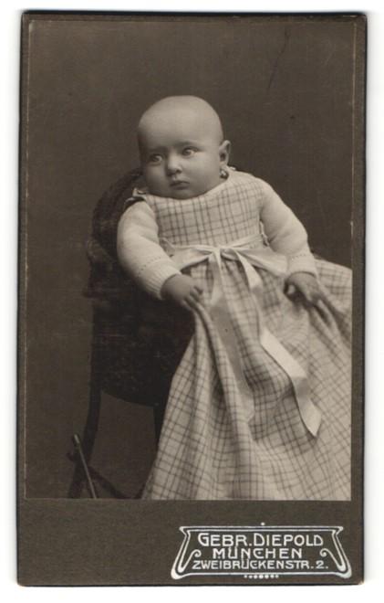 Fotografie Gebr. Diepold, München, Portrait Baby mit Glatzkopf im hübschen Kleid
