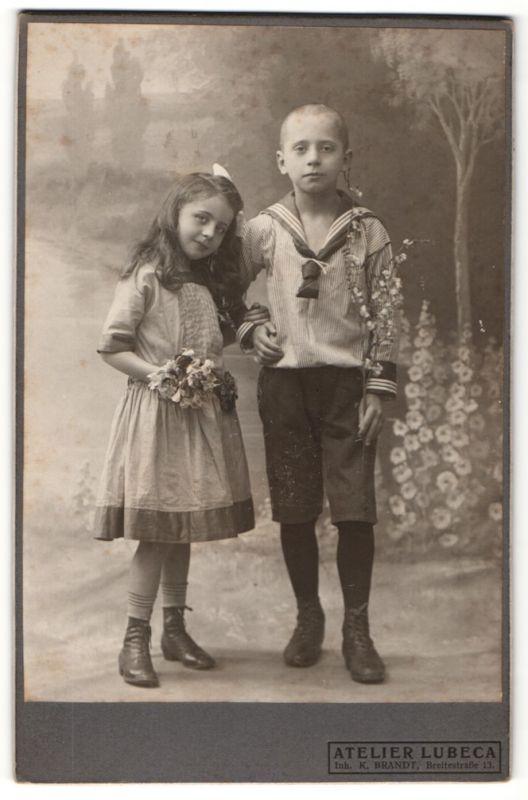 Fotografie Atelier Lubeca, Ort unbekannt, süsses lächelndes Mädchen mit Blumenstrauss & Knabe im Matrosenanzug