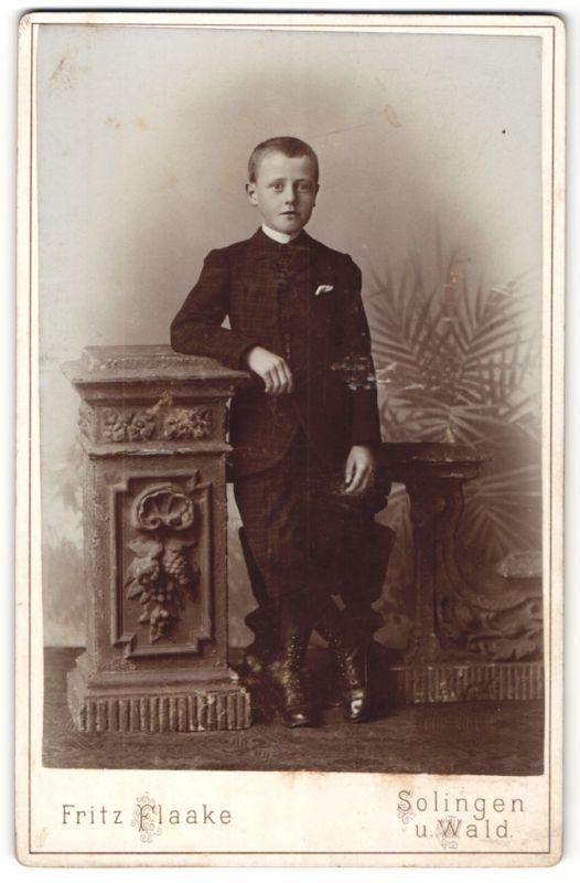 Fotografie Fritz Flaake, Solingen, frecher Bube mit kurzem Haar im schwarzen Anzug und Schnürstiefeln