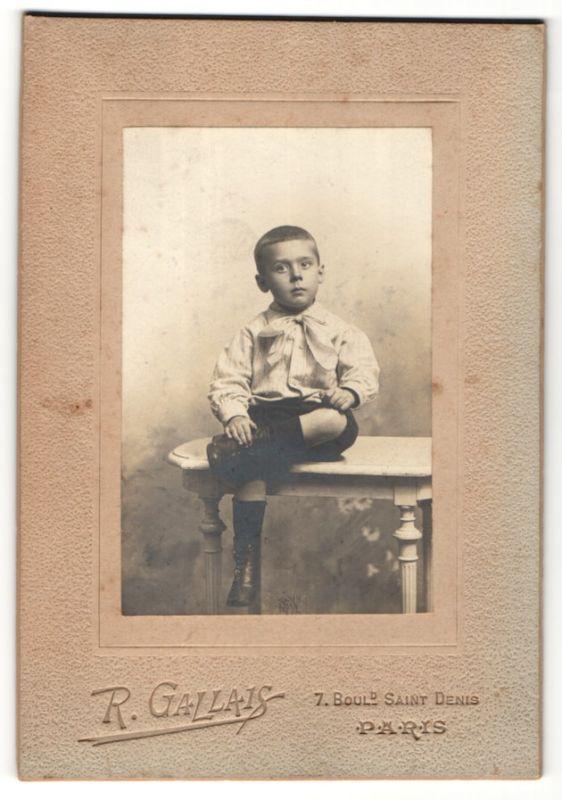 Fotografie R. Gallais, Paris, frecher Bube mit kurzem Haar, Schleife am Kragen und süssen Stiefelchen