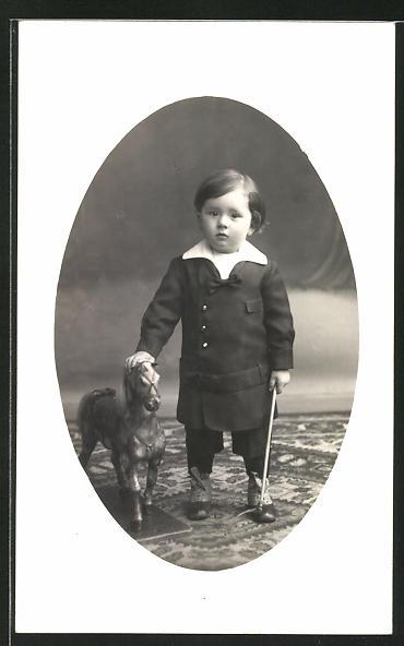 Foto-AK Kleinkind in zeitgenöss. Kleidung mit Spielzeugpferd