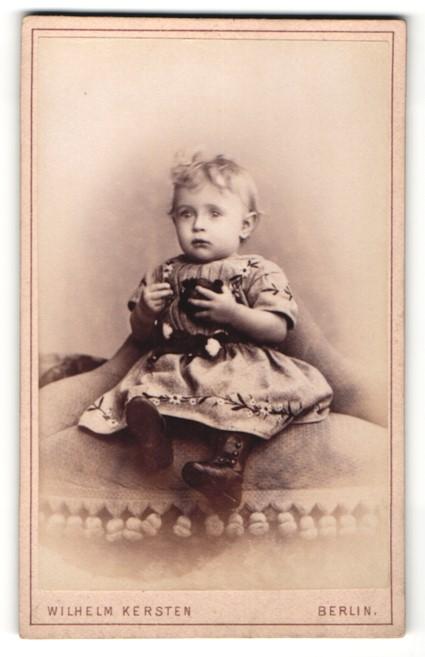 Fotografie Wilhelm Kersten, Berlin, zuckersüsses blondes Mädchen mit Spielzeug im geblümten Kleidchen