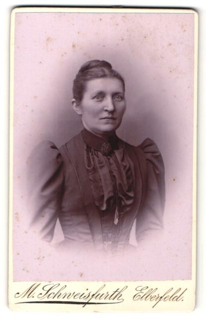 Fotografie M. Schweisfurth, Elberfeld, Portrait charmant blickende Dame mit hochgebundenem Haar und Brosche am Kragen