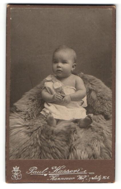 Fotografie Paul Hassert, Hannover, zuckersüsses Baby im weissen Kleidchen mit Spielzeug