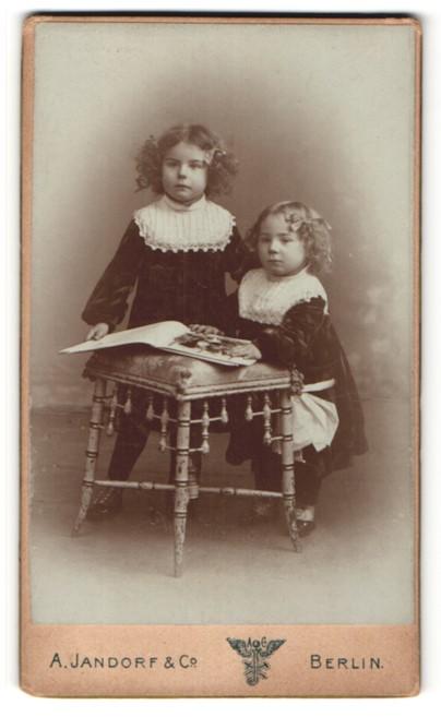 Fotografie A. Jandorf & Co, Berlin, zwei bezaubernde kleine Mädchen mit Haarschleifen und grossem Buch