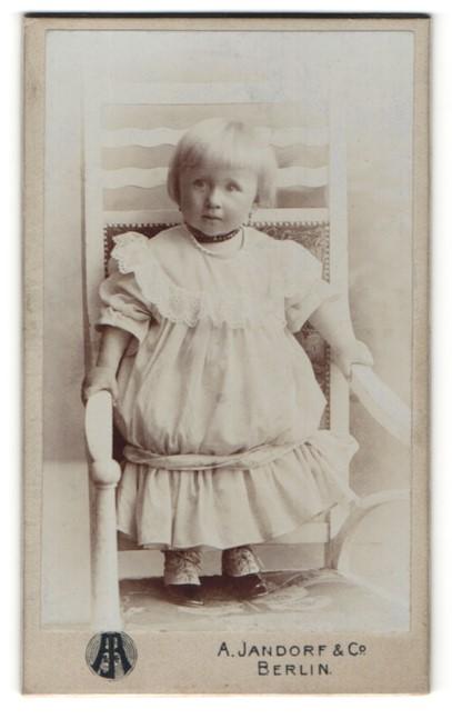 Fotografie A. Jandorf & Co, Berlin, zuckersüsses blondes Mädchen mit Perlenhalskette im weissen Rüschenkleid