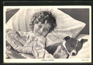 AK Schauspielerin Shirley Temple mit Hund im Bett liegend