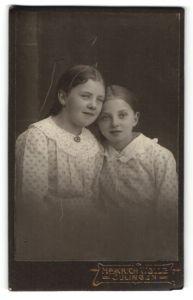 Fotografie Heinrich Wolle, Sulingen, Portrait zwei Mädchen in identischen Kleidern, Schwestern
