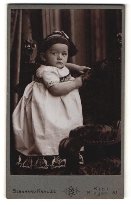 Fotografie Bernhard Krause, Kiel, Portrait Kleinkind mit Mütze in Kleidchen
