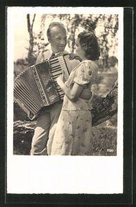 AK Junger Mann spielt für eine Frau auf dem Akkordeon