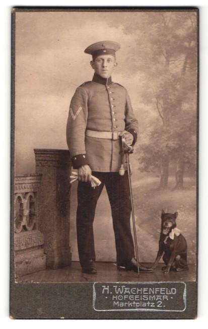 Fotografie H. Wachenfeld, Hofgeismar, Deutscher Soldat in Uniform mit Säbel und Hund im Atelier