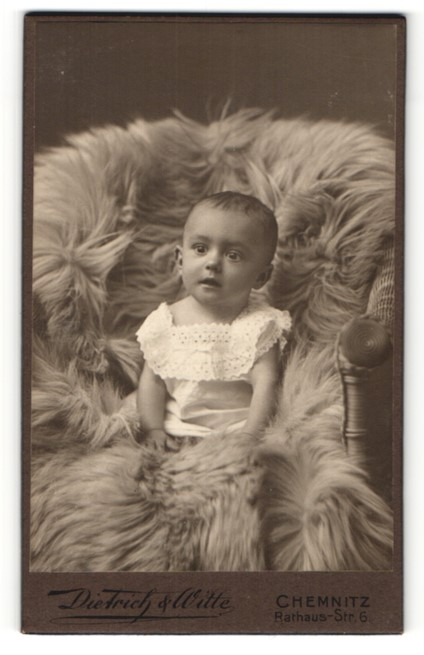 Fotografie Dietrich & Witte, Chemnitz, süss blickendes Kleinkind im weissen Kleidchen auf Felldecke sitzend