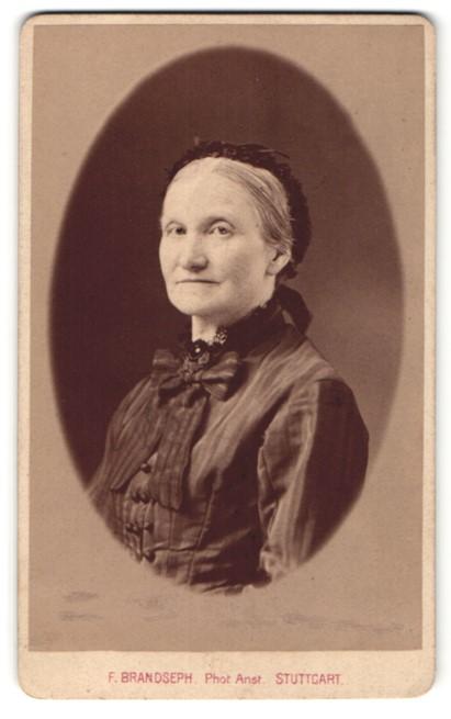 Fotografie F. Brandseph, Stuttgart, Portrait charmant blickende ältere Dame mit Rüschenhaube und Schleife am Kragen