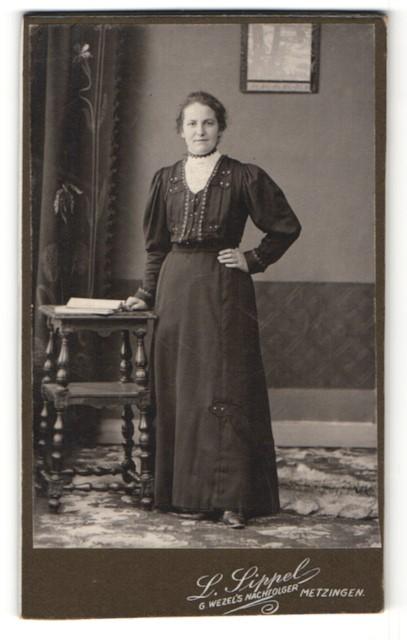 Fotografie L. Lippel, Metzingen, charmant lächelnde Dame im elegant besticktem Kleid mit Buch