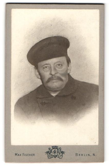 Fotografie Max Fischer, Berlin, Portrait betagter charmanter Herr mit Mütze im Mantel