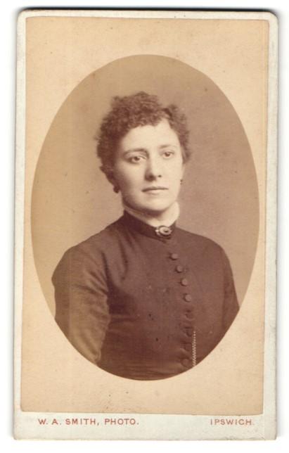 Fotografie W. A. Smith, Ipswich, Portrait charmant blickende junge Dame mit Ohrringen und Brosche am Kragen
