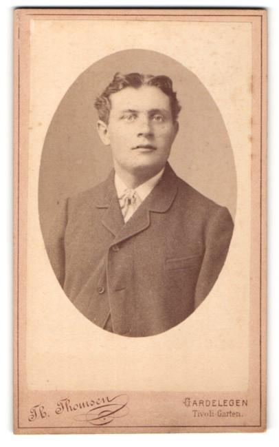 Fotografie Th. Thomsen, Gardelegen, Portrait charmanter junger Mann mit Mittelscheitel und Fliege im Anzug