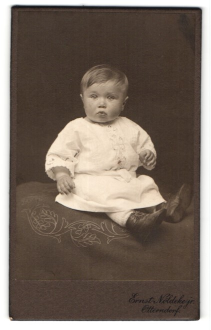 Fotografie Ernst Nöldeke, Otterndorf, zuckersüsses Baby im weissen Kleidchen und Schnürstiefelchen