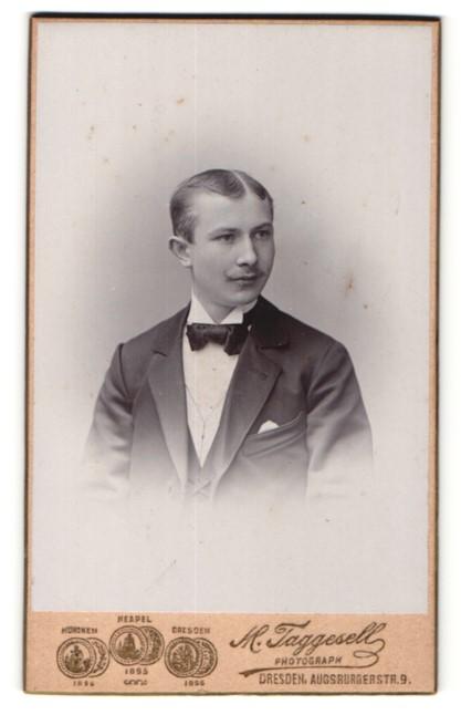 Fotografie M. Taggesell, Dresden, Portrait charmanter junger Mann mit Mittelscheitel und schwarzer Fliege im Anzug