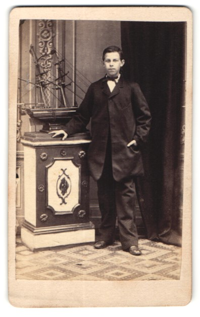 Fotografie Gustav Weber, Hamburg-Altona, junger dunkelhaariger Bube im schwarzen Mantel