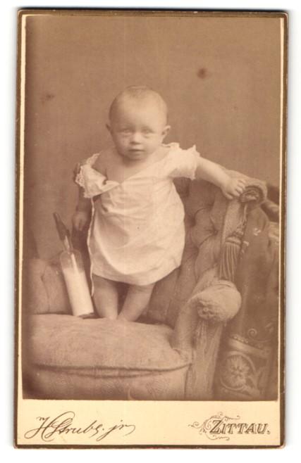 Fotografie H. Strube, Zittau, zuckersüsses kleines Baby im weissen Kleidchen mit Nuckelflasche