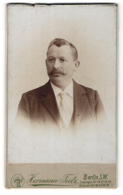 Fotografie Hermann Tietz, Berlin, Portrait eleganter Herr im Anzug mit Krawatte