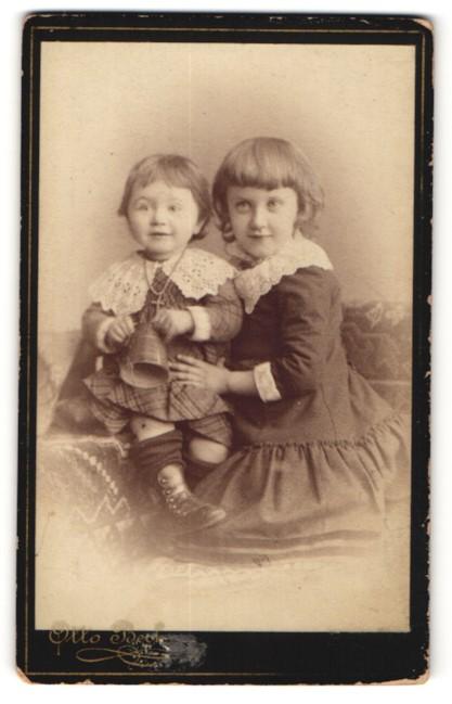 Fotografie Otto Becker, Berlin, zwei bezaubernd süsse Mädchen in tollen Kleidern mit Spielzeug