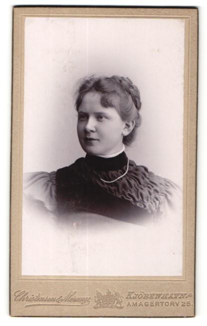 Fotografie Christensen & Morange, Kjöbenhavn, Portrait charmant blickende Dame mit Flechtfrisur und Halskette
