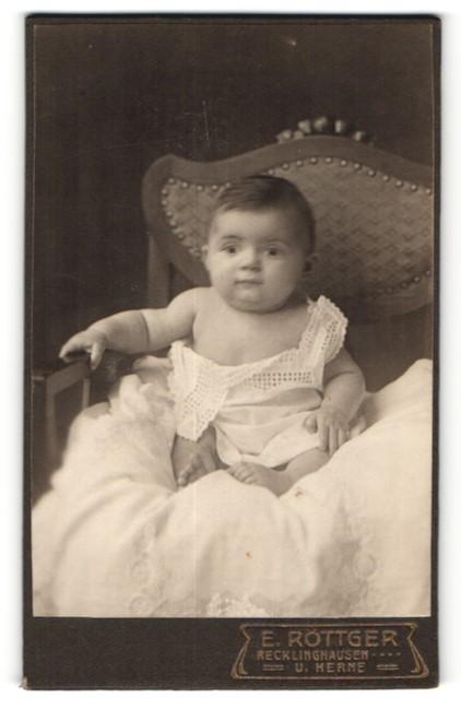 Fotografie E. Röttger, Recklinghausen, zuckersüsses brünettes Baby im weissen Kleidchen
