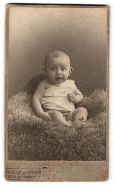 Fotografie Atelier Wertheim, Berlin, bezaubernd süsses Baby im weissen Kleidchen auf Felldecke sitzend