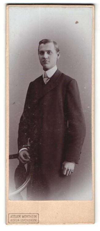 Fotografie Atelier Wertheim, Berlin, Portrait hübscher junger Mann mit zurückgekämmtem Haar im eleganten Mantel
