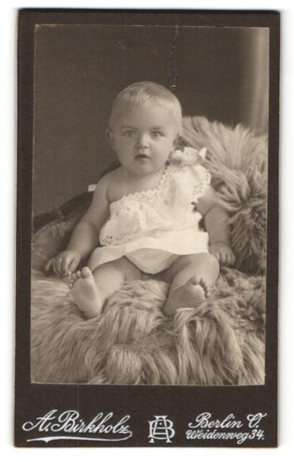 Fotografie A. Birkholz, Berlin, zuckersüsses blondes Mädchen im weissen Kleidchen mit Schleife auf Felldecke sitzend
