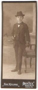 Fotografie Edg. Wallnau, Berlin, hübscher Knabe mit Hut, Buch und Handschuhen im schwarzen Anzug