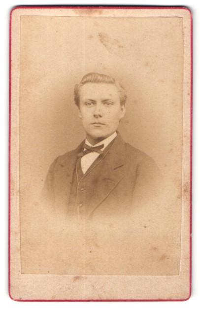 Fotografie Julius Hecht, Schöningen, Portrait hübscher junger Mann mit blondem Haar und Fliege im Anzug
