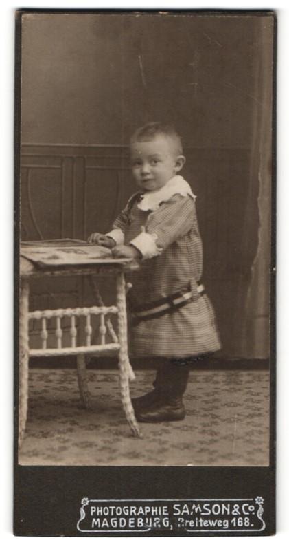 Fotografie Samson & Co, Magdeburg, zuckersüss blickendes Kleinkind mit Zeitschrift im karierten Kleidchen