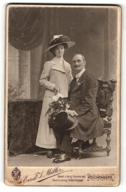 Fotografie Ernst J.Müller, Reichenberg, Mann mit Zylinder in der Hand sitzend neben stehender Frau
